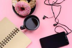 Un bloc-notes des ressorts, une tasse de café, un stylo et un téléphone avec des écouteurs se trouvent sur un fond rose Beau lumi Photos libres de droits