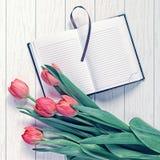 Un bloc-notes ouvert avec un repère et des pages blanches est sur un fond en bois blanc Est en haut un bouquet des tulipes rouges Image libre de droits