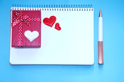 Un bloc-notes, un boîte-cadeau, des coeurs et un stylo sur le fond bleu Images stock