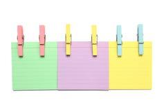 Un blocchetto per appunti di tre colori con le clip di legno Fotografia Stock