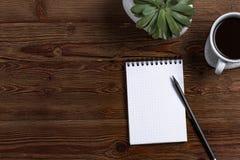 Un blocco note in bianco con la matita, con caffè e la pianta su un fondo di legno fotografia stock