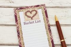 Un blocco note e una penna su fondo di legno stagionato con testo Bucket Fotografia Stock