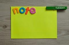 Un blocco note giallo con la nota di parola e un piolo allegato con la parola martedì su  Immagine Stock