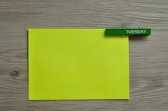 Un blocco note giallo con un piolo allegato con la parola martedì Fotografia Stock Libera da Diritti