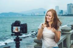 Un blogger de la mujer joven lleva su blog video delante de una cámara por el mar Concepto del Blogger Imagen de archivo