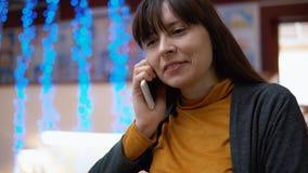 Un blogger de la mujer utiliza el teléfono dentro al lado de las luces eléctricas azules almacen de metraje de vídeo
