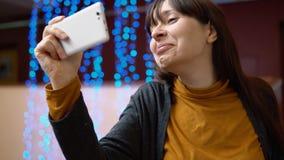 Un blogger de la mujer utiliza el teléfono dentro al lado de las luces eléctricas azules metrajes