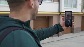 Un blogger maschio cammina giù la via e scrive il contenuto video d archivio