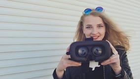 Un blonde elegante joven en una chaqueta de cuero cerca de persianas de rodillo horizontales trae los vidrios virtuales a la cáma almacen de video