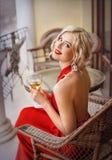 Un blonde hermoso con el lápiz labial rojo, y en un vestido largo rojo, se sienta en el balcón en una tabla de cristal con un vid fotografía de archivo libre de regalías