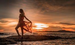 Un blonde hermoso en un vestido rojo claro está haciendo una pausa el mar en un fondo de la puesta del sol brillante imagen de archivo