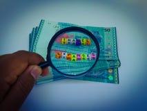 Un bloque de gastos de desplazamiento de la letra, moneda, lupa con un fondo blanco fotos de archivo libres de regalías