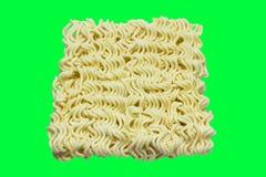Un bloque de tallarines de Ramen crudos aislados en la pantalla verde Fotos de archivo
