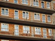 Un bloque nuevamente construido del ladrillo rojo con las ventanas plásticas cubiertas con la hoja, los balcones concretos grises foto de archivo