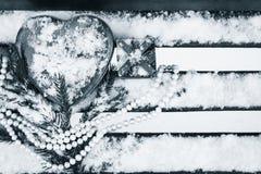 Un boîte-cadeau, boîte en forme de coeur rouge de bidon avec un collier blanc de perle Photo stock