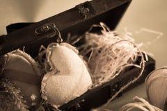 Un boîte-cadeau en bois avec des coeurs de substance et des matériaux d'emballage, sépia Image stock