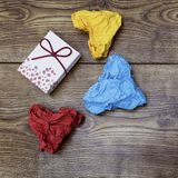 Un boîte-cadeau et trois papiers chiffonnés en forme de coeur colorés sur la table en bois ` S de Valentine Jour du ` s d'amant Image stock