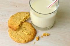 Un bocado de galletas de mantequilla hechas en casa de cacahuete preparadas y de un vidrio fresco de leche listo para beber a tra imagenes de archivo