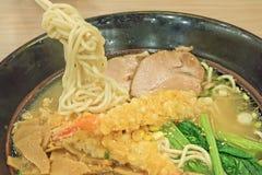 Un bol de soupe de nouilles japonaise avec le tempura de crevette photographie stock