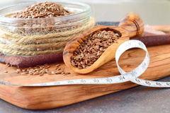 Un bol en verre de graines de lin avec le scoop olive et la bande de mesure sur une planche à découper en bois olive sur le fond  images stock