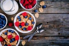 Un bol sain de petit déjeuner Céréale entière de grain avec les myrtilles et les framboises fraîches sur le fond en bois Vue supé Photo libre de droits