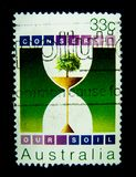 Un bollo stampato in Australia mostra che un'immagine di un albero verde in un orologio della sabbia per conserva la nostra serie Immagine Stock Libera da Diritti