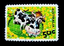 Un bollo stampato in Australia mostra un'immagine del fumetto sveglio della mucca sul valore al centesimo 50 Fotografia Stock Libera da Diritti