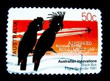 Un bollo stampato in Australia mostra un'immagine dell'uccello delle cacatue della siluetta due per la serie del bollo di innovaz Fotografia Stock Libera da Diritti
