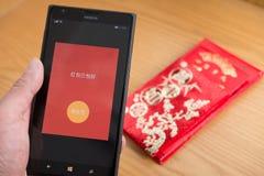 Un bolsillo rojo en móvil está listo para ser enviado en WeChat por Año Nuevo chino con los bolsillos rojos reales en fondo Fotografía de archivo
