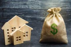 Un bolso con el dinero y las casas de madera Venta de una casa Compra del apartamento Mercado inmobiliario Vivienda de alquiler p foto de archivo libre de regalías
