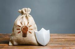 Un bolso con ideas o patentes y un escudo El concepto de protecci?n de los derechos reservados y de las patentes para las invenci imagen de archivo