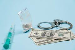 Un bolso de drogas, de dólares de EE. UU. y de esposas en la tabla imagen de archivo libre de regalías