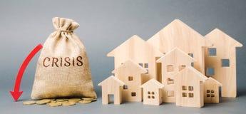 Un bolso del dinero con la crisis de la palabra, una flecha abajo y las casas de madera Concepto de mercado inmobiliario que cae  imágenes de archivo libres de regalías