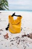 Un bolso impermeable en la playa Foto de archivo libre de regalías