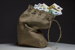 Un bolso lleno de euros en una tabla imágenes de archivo libres de regalías