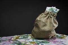 Un bolso lleno de euros en una tabla blanca foto de archivo libre de regalías