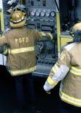 Un bombero trabaja las bombas de un coche de bomberos en un fuego imagen de archivo