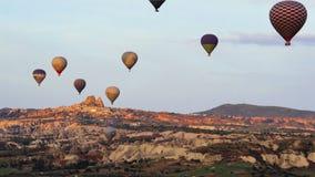 Un bon nombre de ballons à air chauds volant au-dessus des vallées dans Goreme, Turquie Les touristes de partout dans le monde vi banque de vidéos