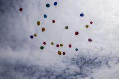 Un bon nombre de ballons colorés volant dans le ciel bleu avec le clou blanc Images stock
