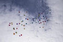 Un bon nombre de ballons colorés volant dans le ciel bleu avec le clou blanc Photographie stock