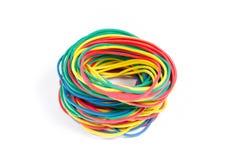 Un bon nombre de bandes élastiques de couleurs rouges, bleues, jaunes et vertes Image stock