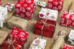 Un bon nombre de boîte-cadeau sur le fond en bois Présents dans le métier et le col Photo libre de droits