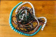 Un bon nombre de brins de perle de diverses couleurs s'étendant sur une table en bois Photos libres de droits