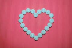 Un bon nombre de comprimés convexes lisses bleus avec la bande de division sur le fond rayé rose, sous forme de coeur image stock