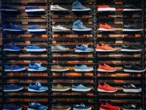 Un bon nombre de différentes espadrilles sur l'étalage sur le marché Image des chaussures de sport sur la vitrine Image libre de droits