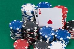 Un bon nombre de jetons de poker et de deux cartes de gain sur la table verte photo stock