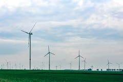 Un bon nombre de moulins à vent sur un champ vert Photographie stock