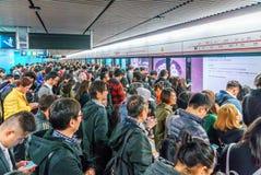 Un bon nombre de peuple chinois occupé se serrant à la station de métro dans le secteur central de Hong Kong attendant un train p images libres de droits