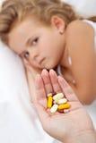 Un bon nombre de pillules pour une petite fille malade Image libre de droits