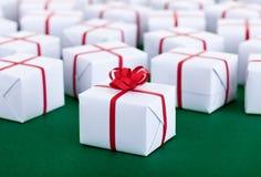 Un bon nombre de présents dans des boîte-cadeau blancs - sur la surface verte Photos libres de droits